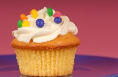 cupcake with buttercream frosting and colored chocolates