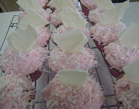 cupcakes with pink buttercream frosting and and coconut and white chocolate